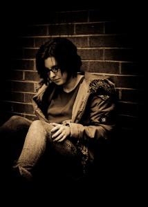 Young person sitting against wall